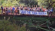 "People holding ""Save the Yuba River"" sign across bridge"