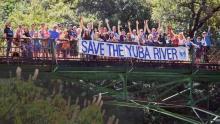 "People holding ""Save the Yuba River"" sign across bridge"