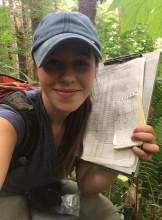 Woman holding binder in forest, smiling