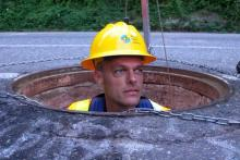 Stokley's head popping out of a manhole in the street