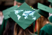 A student's graduation cap decorated with a world map.