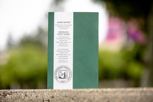 The back of 2020 Graduation program as the program rests on a ledge, the lyrics to the alma mater visible