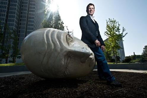 Chris Baggott, in a suit, sits outside on a sculpture