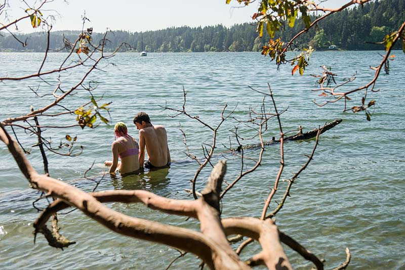 Two students sit in the waters at Evergreen Beach